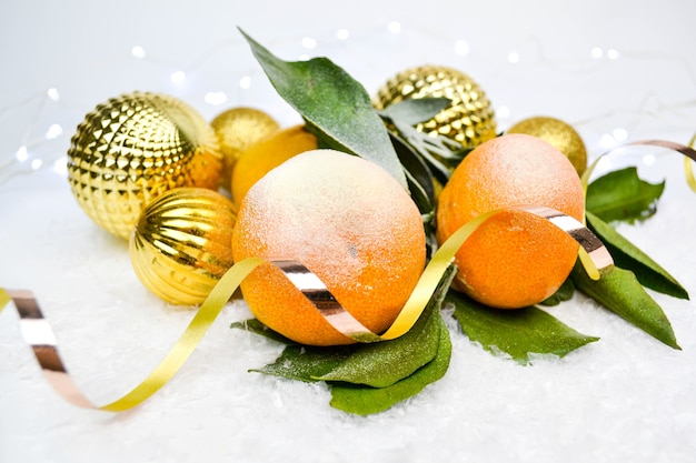 Mandarini, palle di natale d'oro nella neve