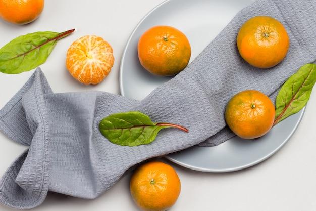 Mandarini su tovagliolo grigio e lastra grigia. lay piatto