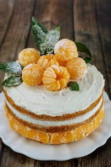 Torta nuda di mandarini con foglie su fondo rustico.