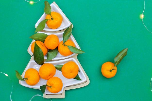 Mandarini a forma di albero di natale su uno sfondo verde. sfondo di cibo di natale, vista dall'alto. un divertente albero di natale commestibile