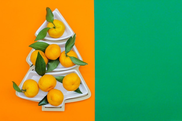 Mandarini a forma di albero di natale su uno sfondo verde-arancio. sfondo di cibo di natale, vista dall'alto. un divertente albero di natale commestibile.
