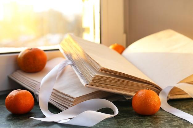 Mandarini e libri vintage su un tavolo di marmo vicino alla finestra in inverno