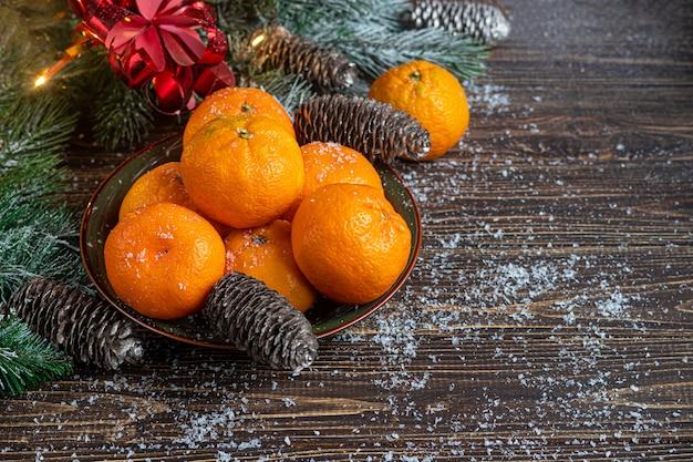 Mandarini su un tavolo in legno con rami di un albero di natale e pigne ricoperte di neve.