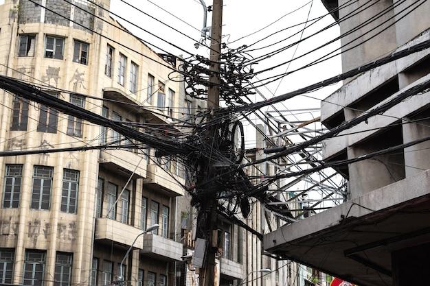 Groviglio di cavi elettrici e cavi di comunicazione sul palo elettrico.