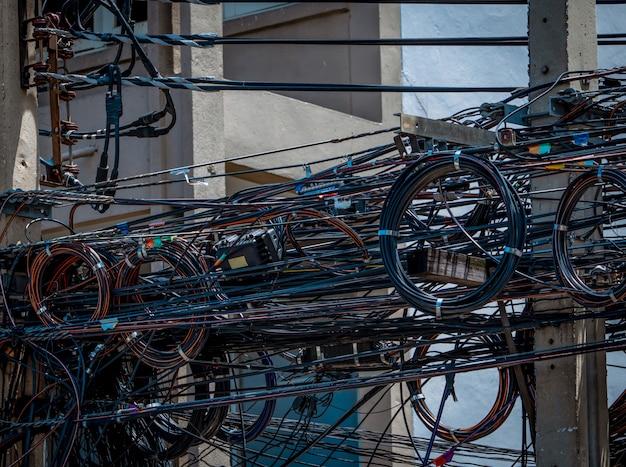 Cavi elettrici aggrovigliati sul palo elettrico urbano