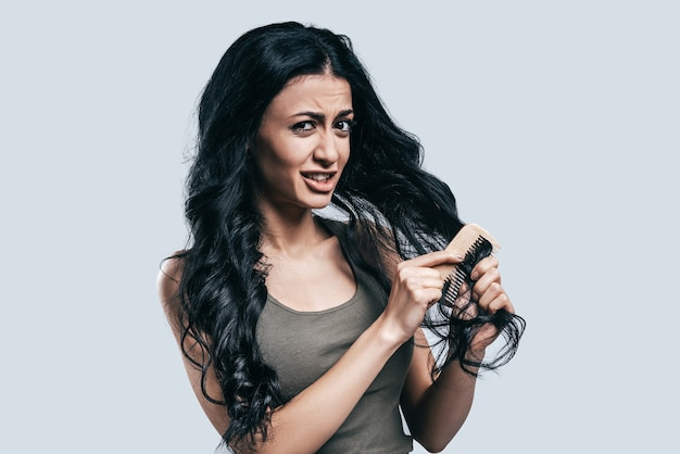 Capelli arruffati. attraente giovane donna in abbigliamento casual che si pettina i capelli e guarda la telecamera mentre è in piedi su sfondo grigio gray