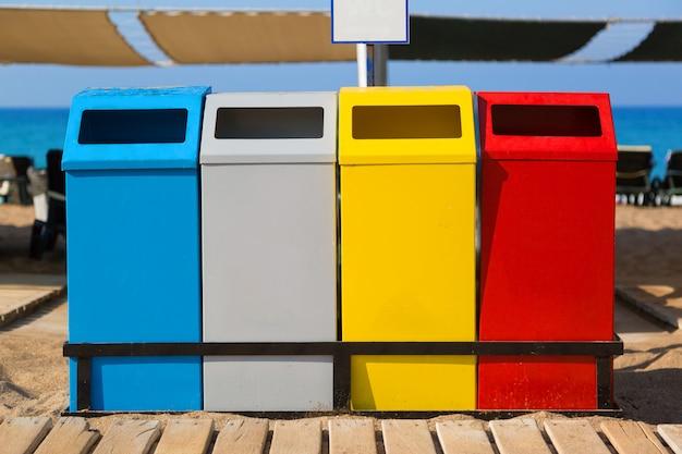 Contenitori di serbatoi di diversi colori per la raccolta differenziata di rifiuti e immondizia sulla spiaggia del mare.