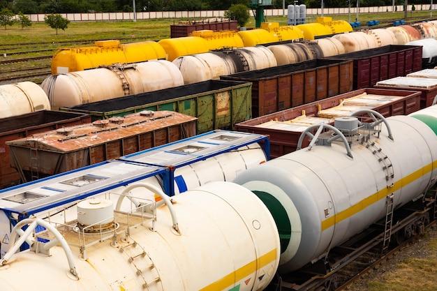 Cisterne con carburante, vagoni con merci in una stazione ferroviaria merci.