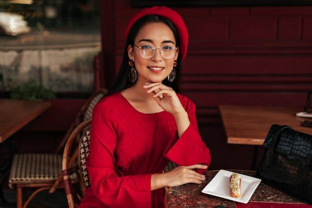 La donna asiatica abbronzata in berretto rosso, vestito luminoso e occhiali da vista sorride, si siede in uno splendido caffè e guarda nella telecamera