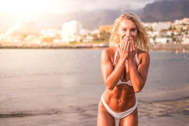Corpo sexy ragazza abbronzata sorridi e goditi le vacanze estive inviando baci. ragazza perfetta fitness in spiaggia durante le vacanze. allegra giovane donna con il sole in controluce durante il tramonto