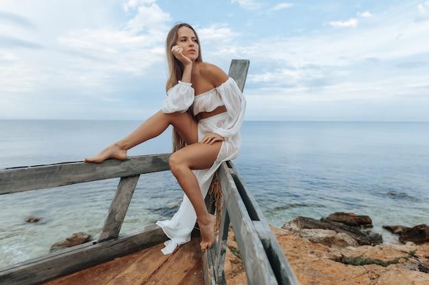 Una ragazza abbronzata con un vestito bianco sexy siede sulla prua di una nave distrutta sulla spiaggia