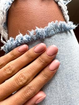 Mano abbronzata di una donna con una delicata manicure beige-rosa, che copre con smalto gel