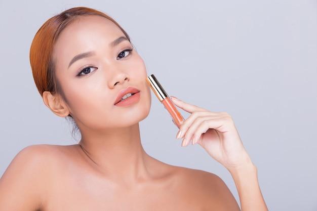 Pelle abbronzata giovane moda donna asiatica modello presente che mostra cosmetici make up pacchetto prodotti spazio copia vuoto sul palmo della mano, girare la vista posteriore laterale aperta spalla in topless, pubblicità illuminazione studio
