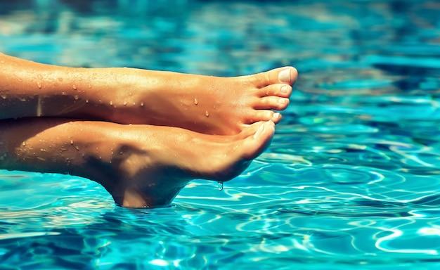 Piedi di donna incrociati ben curati abbronzati coperti da gocce di acqua pulita sta riposando sopra la superficie in movimento blu del waterpool