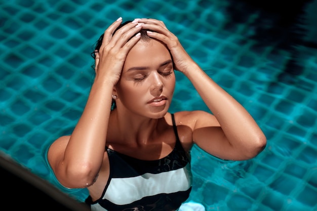 Donna abbronzata in un costume da bagno a righe in piscina