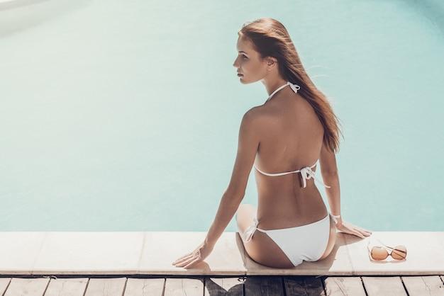 Abbronzatura a bordo piscina. vista posteriore di una giovane donna attraente in bikini bianco seduta a bordo piscina e guardando lontano