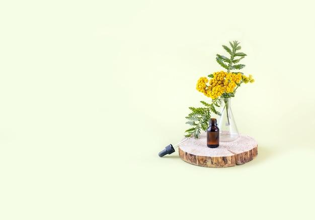 Fiori di tanaceto e una bottiglia di olio d'oliva su un albero tagliato
