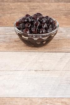 Tapioca pearl, bubble topping per tè o altra bevanda, in una tazza, posto su un tavolo di legno. copia spazio