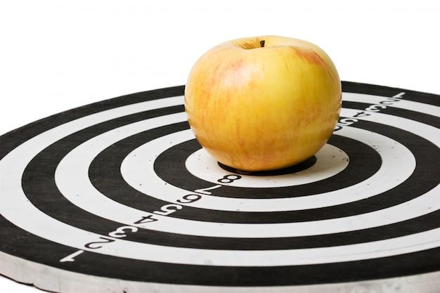 Obiettivo e mela isolati su una superficie bianca