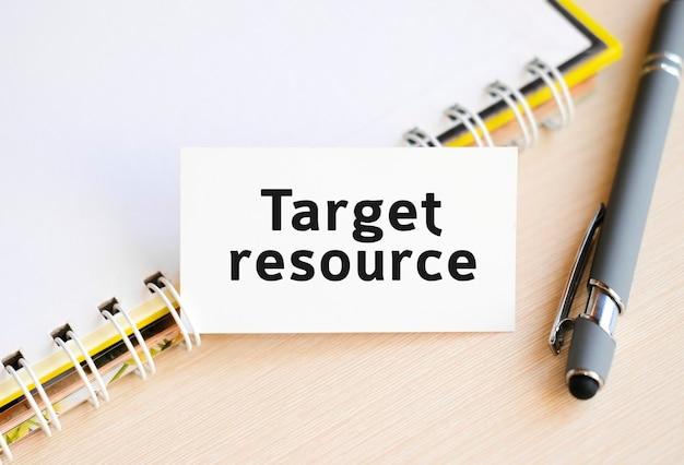 Target del testo della risorsa su un taccuino con una molla e una penna grigia