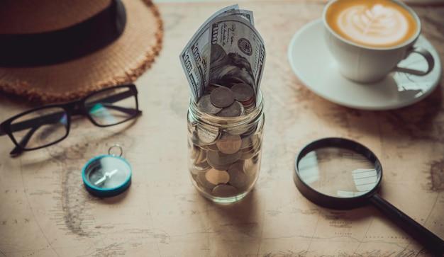 Obiettivo per il viaggio - concetto di risparmio di denaro in un bicchiere e accessori sulla mappa