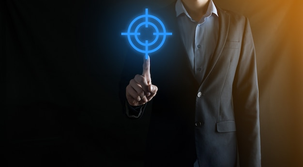 Concetto di targeting con mano di uomo d'affari che tiene schizzo bersaglio icona bersaglio sulla lavagna. obiettivo obiettivo e concetto di obiettivo di investimento.