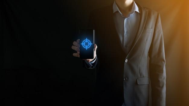 Concetto di targeting con la mano dell'uomo d'affari che tiene lo schizzo del bersaglio per le freccette dell'icona sulla lavagna. obiettivo obiettivo e concetto di obiettivo di investimento.
