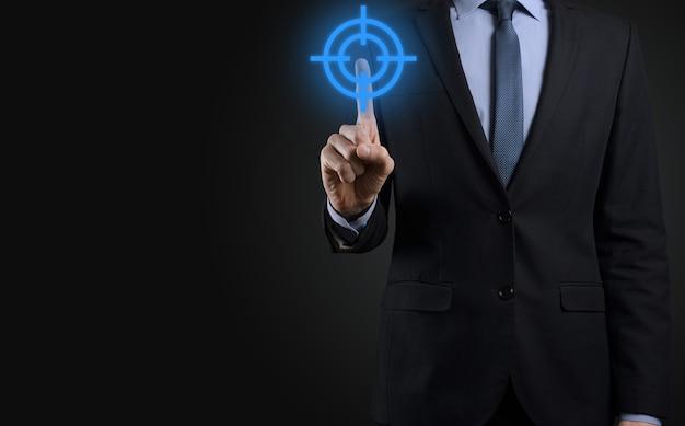 Concetto di targeting con la mano dell'uomo d'affari che tiene lo schizzo del bersaglio icona bersaglio sulla lavagna. obiettivo obiettivo e concetto di obiettivo di investimento.
