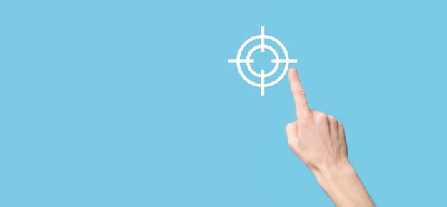 Concetto di targeting con la mano che tiene lo schizzo del bersaglio per le freccette dell'icona sulla lavagna. obiettivo obiettivo e concetto di obiettivo di investimento.