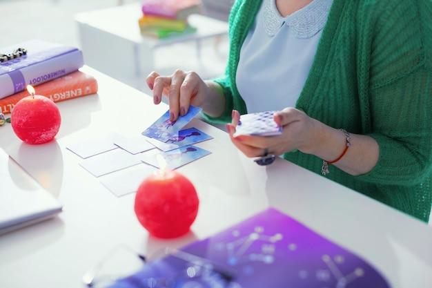 Le carte dei tarocchi nella predizione del futuro. vista dall'alto delle carte dei tarocchi che vengono messe sul tavolo mentre un indovino professionista