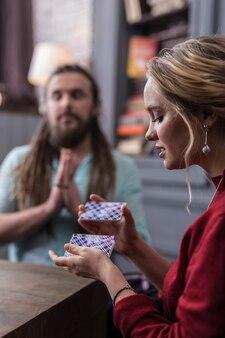 Pacchetto di carte dei tarocchi. bella giovane donna che mescola le carte dei tarocchi mentre pensa al suo destino