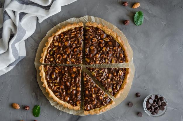 Crostata con cioccolato caramello, nocciole, arachidi, mandorle e mix di semi
