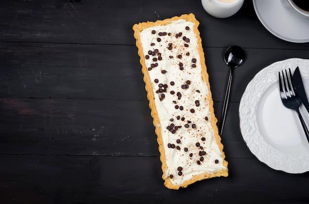Crostata con crema alla vaniglia o cheesecake con gocce di cioccolato e tazza di caffè sul vecchio tavolo di legno scuro,