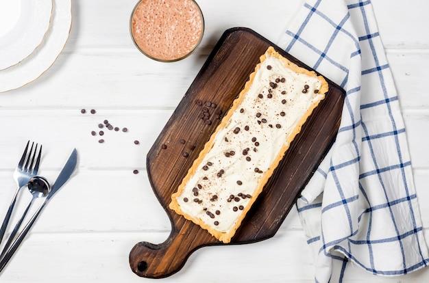 Crostata con crema alla vaniglia o cheesecake con gocce di cioccolato e tazza di caffè sul tavolo di legno bianco,