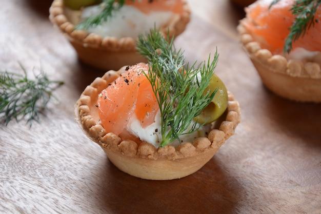 Tartalets con salmone fresco, crema di formaggio philadelphia, olive su fondo di legno