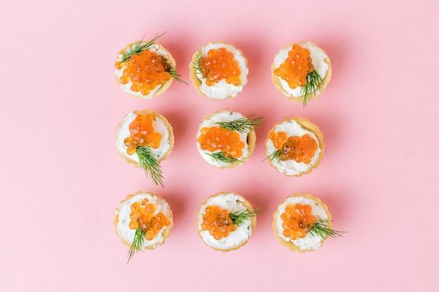 Tortine ripiene di caviale rosso e crema di formaggio su una superficie rosa. antipasto con prelibatezze di mare.