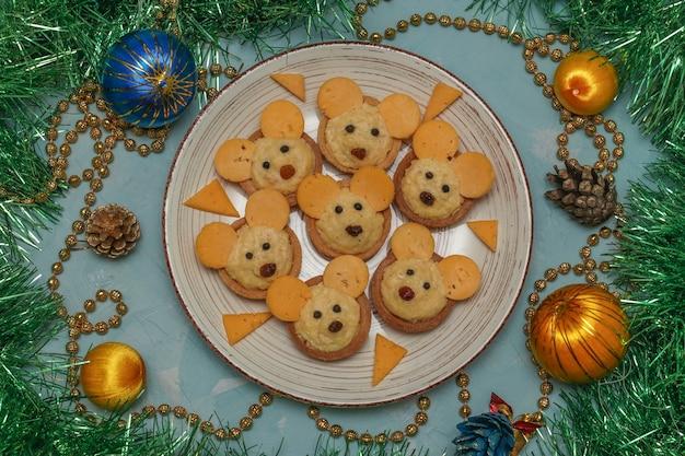 Tartellette topi con formaggio per il nuovo anno su un piatto su sfondo azzurro, orientamento orizzontale