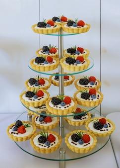 Mini dessert di tortine su supporto acrilico a quattro livelli.