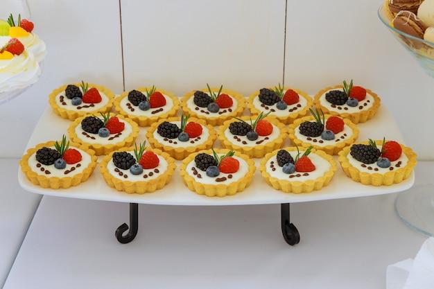 Mini dessert di tortine con frutta fresca su supporto.