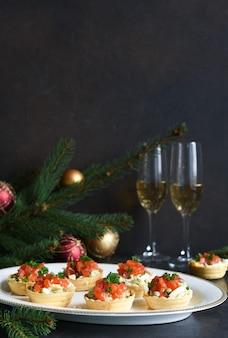 Tortine ripiene di insalata e salmone su un tavolo di capodanno. tavola festiva con un bicchiere di champagne