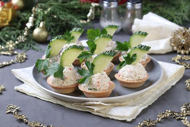 Tortine con bastoncini di granchio, crema di formaggio e cetriolo su un piatto su sfondo grigio