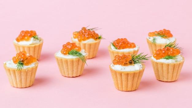 Tortine con crema di formaggio, caviale ed erbe su una superficie rosa. antipasto con prelibatezze di mare.