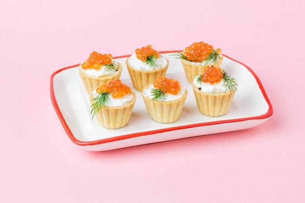Tortine con crema di formaggio, aneto e caviale rosso su una superficie rosa. antipasto con prelibatezze di mare.