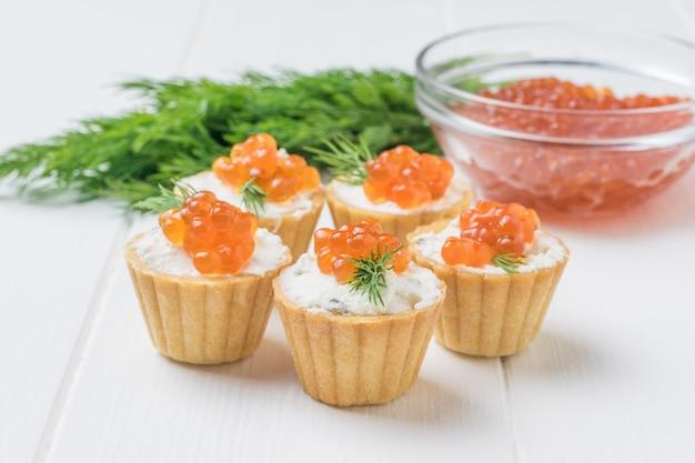 Tortine con ripieno e una ciotola di vetro con caviale rosso su un tavolo bianco. antipasto con prelibatezze di mare.