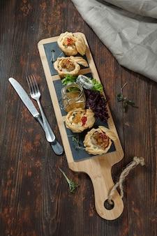 Sul tavolo ci sono tortine con patè di fegato di fegatini di anatra o di pollo e una salsa di olivello spinoso.