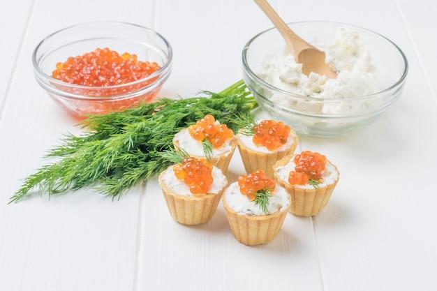 Tortine con caviale rosso e una ciotola di vetro con ricotta su un tavolo di legno bianco. antipasto con prelibatezze di mare.