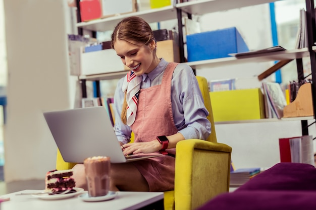 Degustazione di torta al cioccolato. sorridente ragazza positiva con orologio elettronico al polso che lavora con il computer portatile