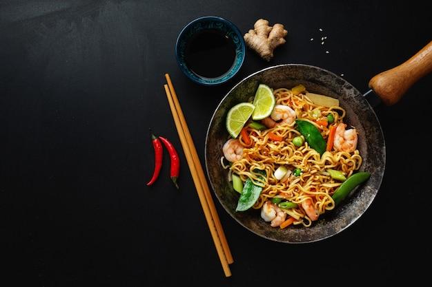 Gustosi spaghetti asiatici appetitosi con verdure e gamberetti in padella sulla superficie scura