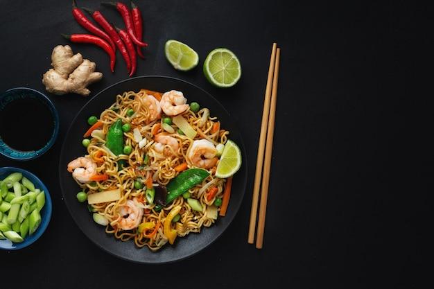 Gustosi spaghetti asiatici appetitosi con verdure e gamberetti sulla piastra sulla superficie scura