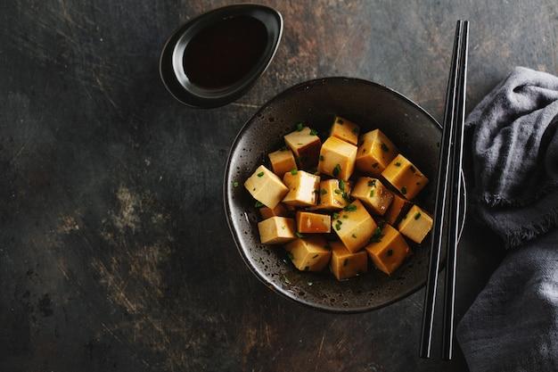 I bei pezzi appetitosi del tofu con salsa sono servito in ciotola pronta per il cibo. avvicinamento.
